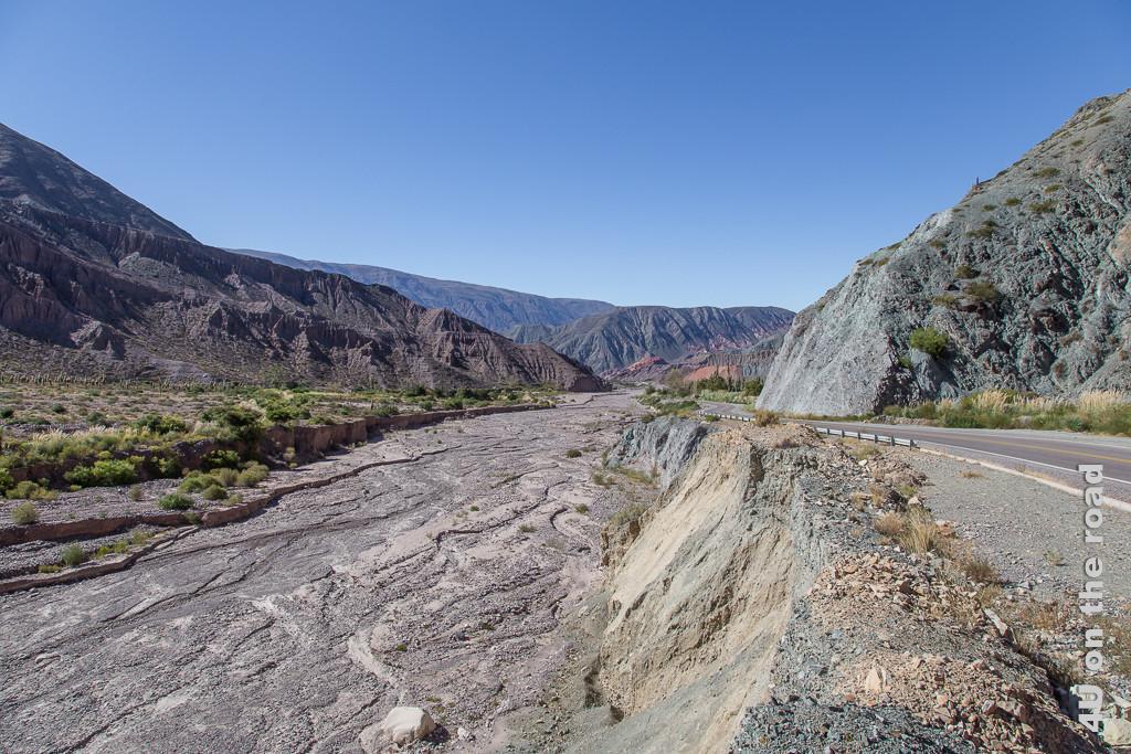 Bild Von Purmamarca zum Passo de Jama entlang des Flusstales - Das Bild zeigt das ausgetrocknete Flussbett neben der Strasse und die verwitterten Felsen
