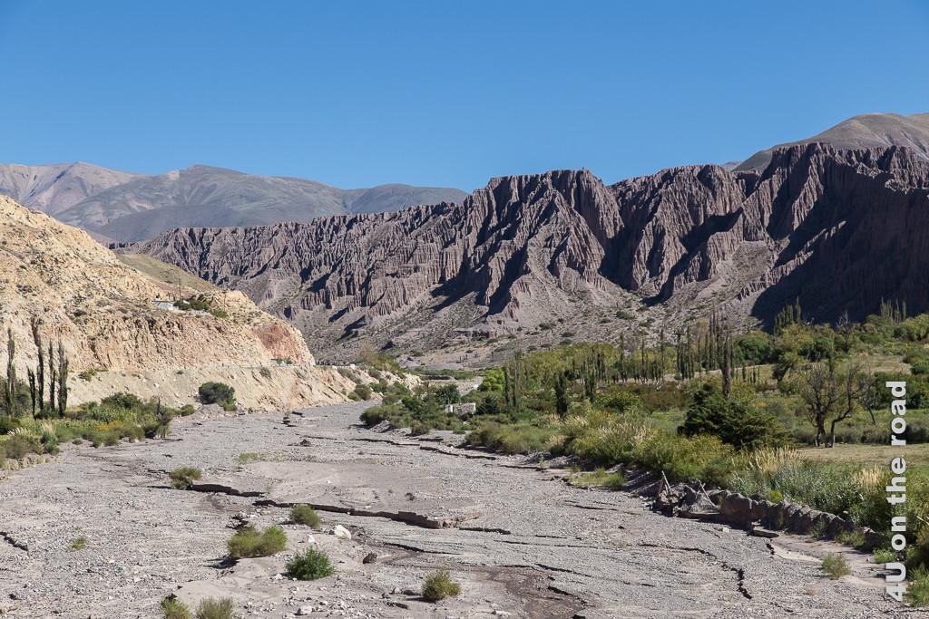 Bild Von Purmamarca zum Passo de Jama- scharfkantige Felsen und grünes Tal zeigt das trockene Flussbett eingerahmt von Felsen und einem grünen Tal mit Bäumen, Gräsern und einem Haus