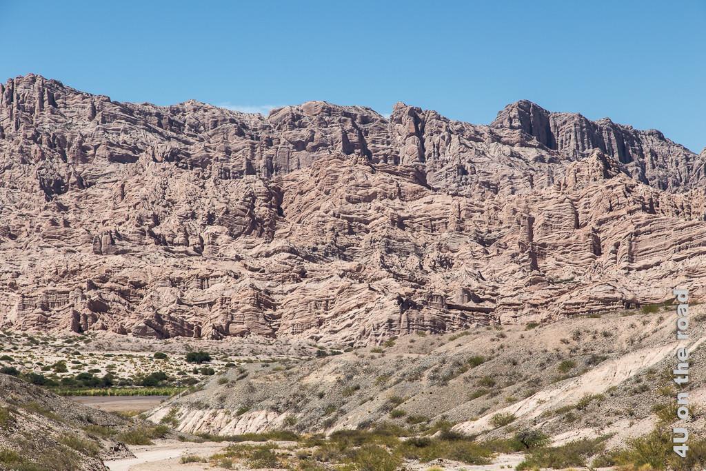 Bild spektakuläre Felsen am gegenüberliegenden Ufer im Valle Calchaquies. Ein rotbraunes Felsgewirr wild verwittert in allen Richtungen.