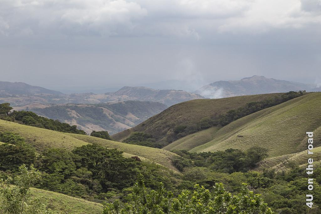 Bild Auf dem Weg nach Monteverde zeigt die hügelige Landschaft mit Rauch und dunklen Wolken