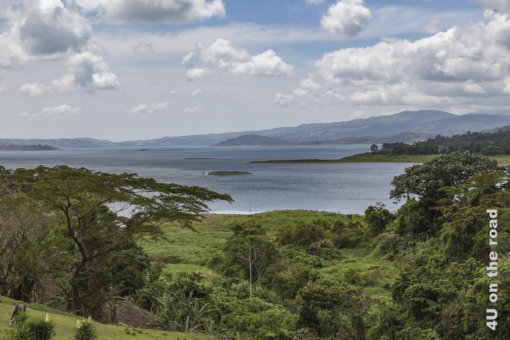 Bild Blick auf den Stausee zeigt den Stausee mit kleinen Inseln, tropische Vegetation und einen bewölkten Himmel