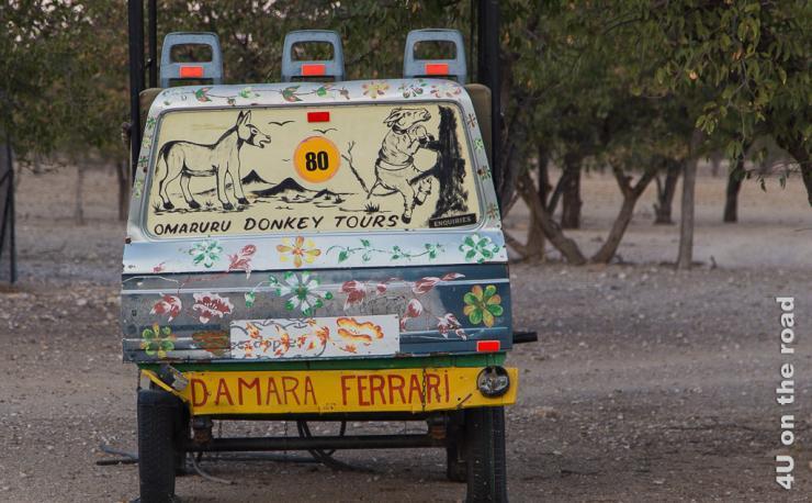 Das Bild zeigt einen Damara Ferrari, eine alte Autokarosse mit Eselsbildern auf der Heckscheibe und Blümchen. Dies ist die Verkleidung für einen Eselskarren.