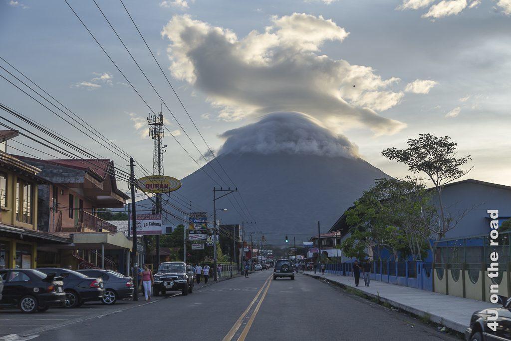 Bild La Fortuna mit Vulkan Arenal im Abendlicht, zeigt den Vulkan mit einer dicken Wolkenmütze auf der Spitze