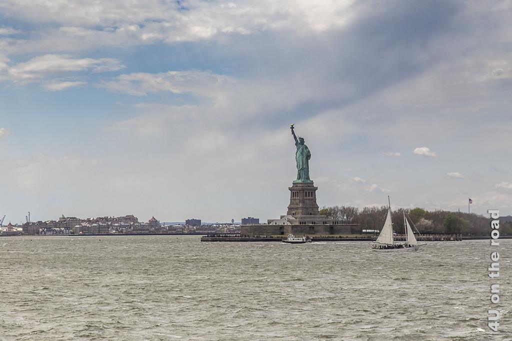 Bild Freiheitsstatue, New York, zeigt die Statue vom Wasser aus gesehen, mit einem Segelschiff und einem kleineren Schiff im vordergrund. Im Hintergrund Stadt.