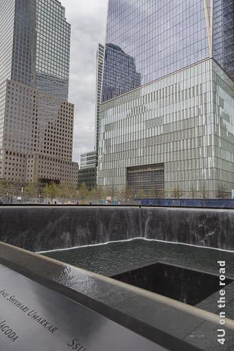 Bild Gedenkbrunnen WTC zeigt im Vordergrund das schwarze Viereck mit dem Wasser, welches an den Seiten herunterrinnt und in der Mitte verschwindet. Im Hintergrund Hochhäuser.