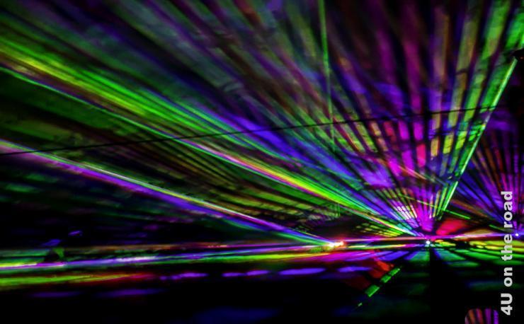 Bild Lasershow zeigt farbige Streifen, die sich längs und diagonal überlagern in den Farben, grün, gelb, rot, violett und blau
