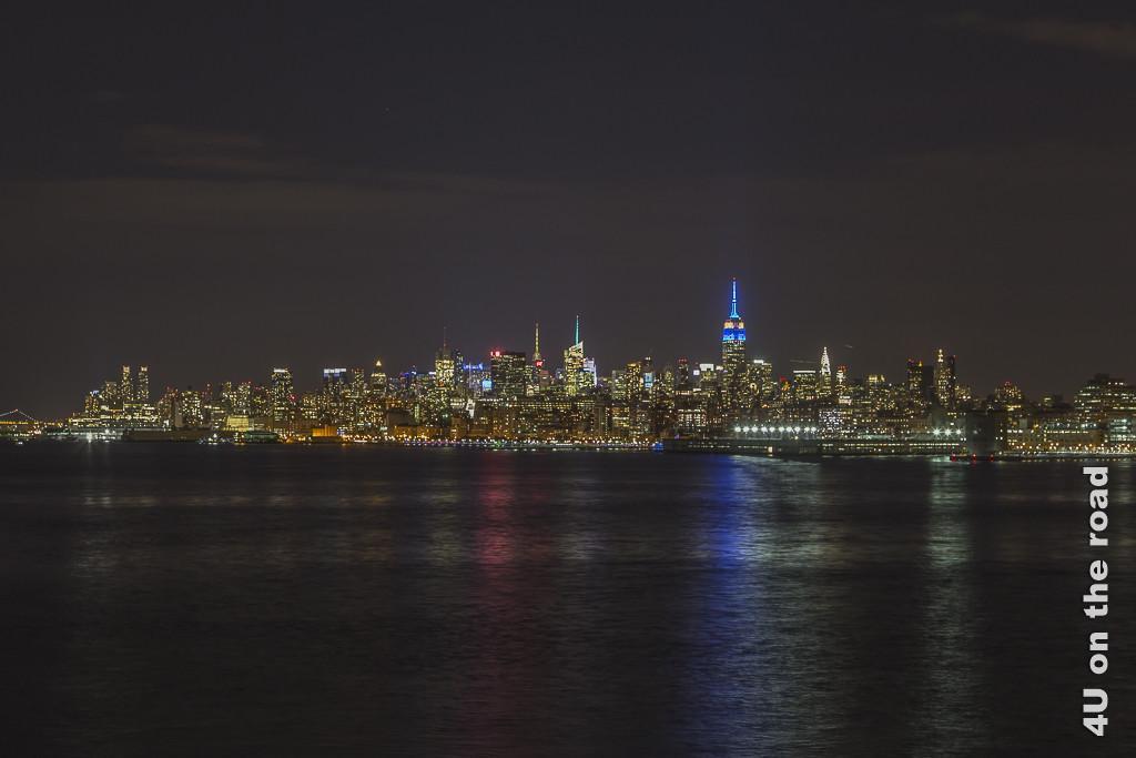 Bild Manhattan bei Nacht zeigt die farbig glitzernde Stadt in der Dunkelheit mit Farbreflexionen im Wasser