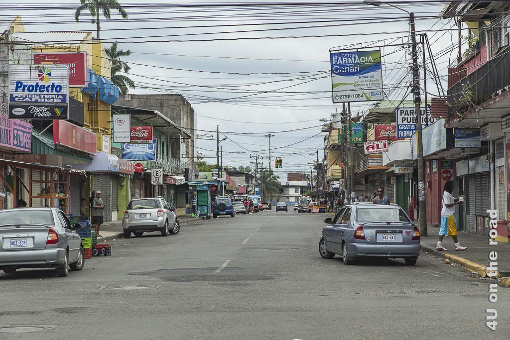 Bild Strasse in Puerto Limón zeigt bunte Werbung an einem Gemisch von Wellblech- und Steinhäusern, einen Himmel voller Kabeln, Autos, Abfall und Menschen.