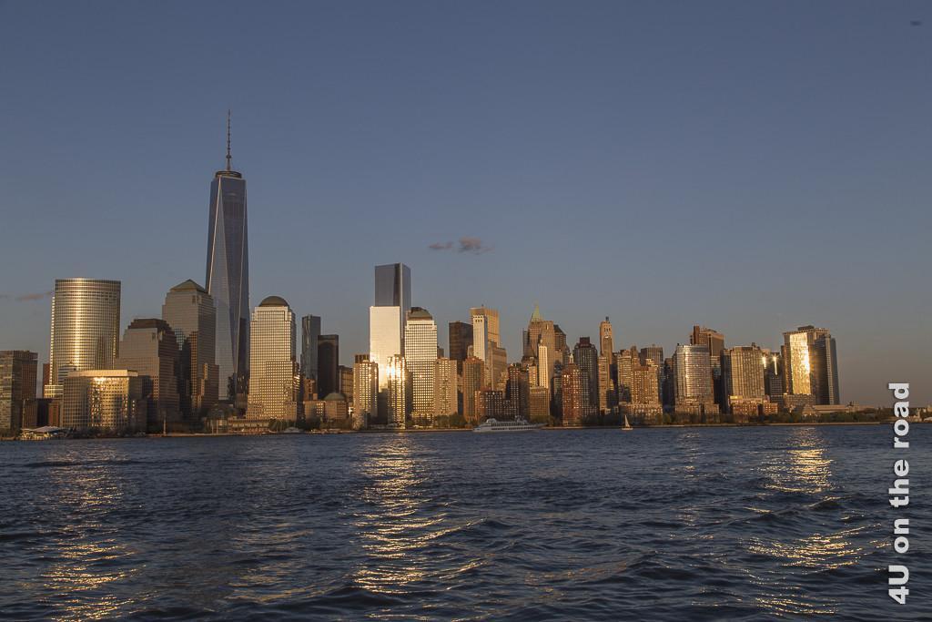 Bild Manhattan im Licht der untergehenden Sonne zeigt die Wolkenkratzer in warmes Licht getaucht mit Sonnenreflexionen im Wasser