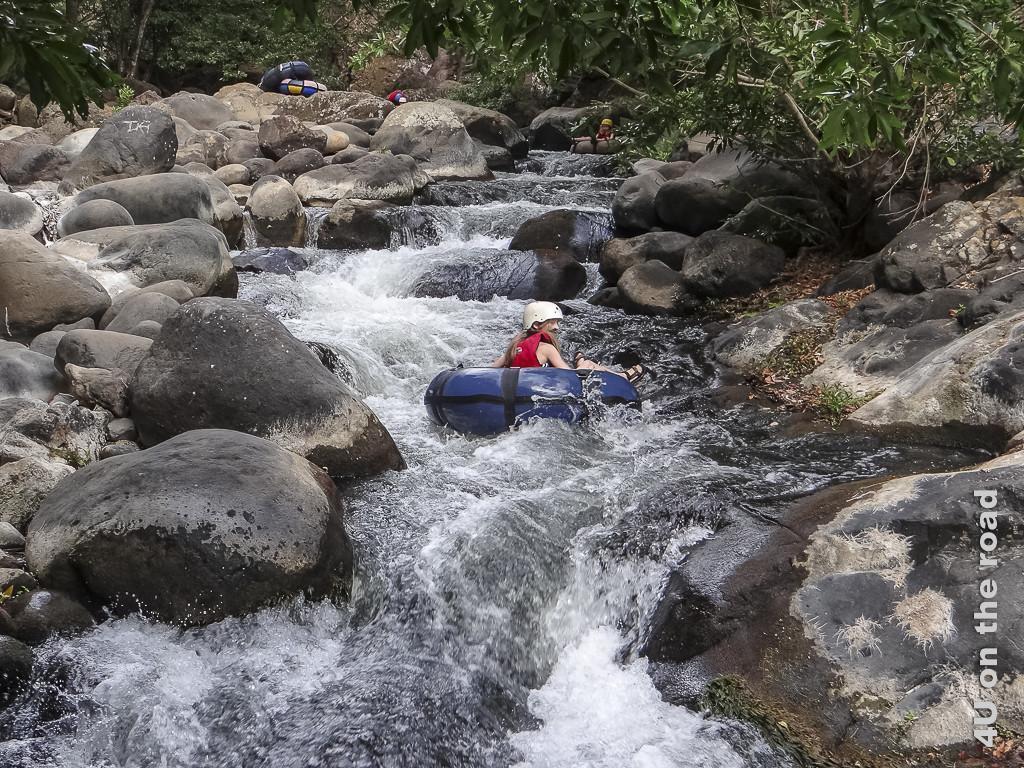 Bild Stromschnelle, trotz wenig Wasser recht schnell zeigt wie in grossen aufgeblasenen Reifen sitzende Personen den Fluss in den Stromschnellen heruntertreiben