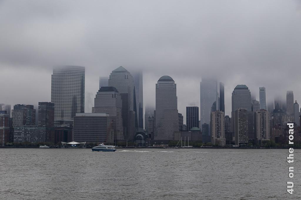 Bild New York's Wolkenkratzer in den Wolken, zeigt die Hochhäuser, deren oberen Stockwerke von den unterschiedlich tiefen Wolkenfetzen verborgen werden