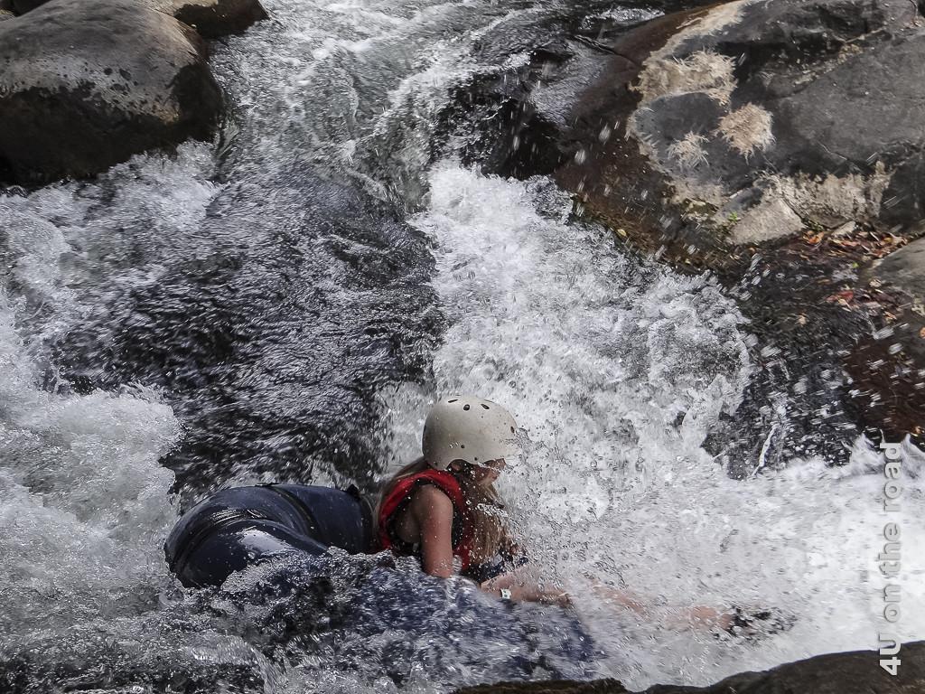 Bild gleich geht es einen kleinen Wasserfall hinunter, zeigt Person im spritzenden Wasser