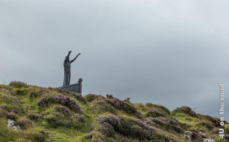 Bild Skulptur von Manannan Mac Lir, einem Meeresgott zeigt einen durchtrainierten Mann mit zum Himmel erhobenen Händen mit einem Schwert an der Seite in einem Boot stehend.