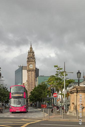 Bild Albert Memorial Clock Tower, Belfast zeigt im Vordergrund einen roten Doppelstockbus und im Hintergrund, den an Big Ben erinnernden Uhrturm.