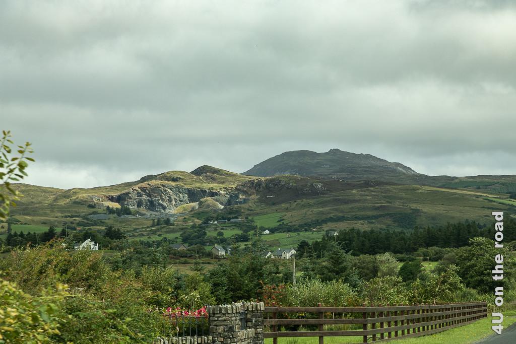 Bild Auf dem Weg nach Milford zeigt einen grösseren sanften Hügel und etwas seitlich versetzt einen Hügel mit Steinbruch, davor grüne Weiden und hübsche Häuser.