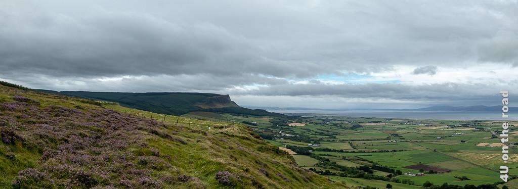 Bild Aussicht vom Gortmore Viewpoint, Bishops Road zeigt sanfte und steile Klippen, teilweise mit blühender Heide bewachsen und das durch Hecken, Mauern und Strassen unterteilte Land, Wasser und dahinter Berge.