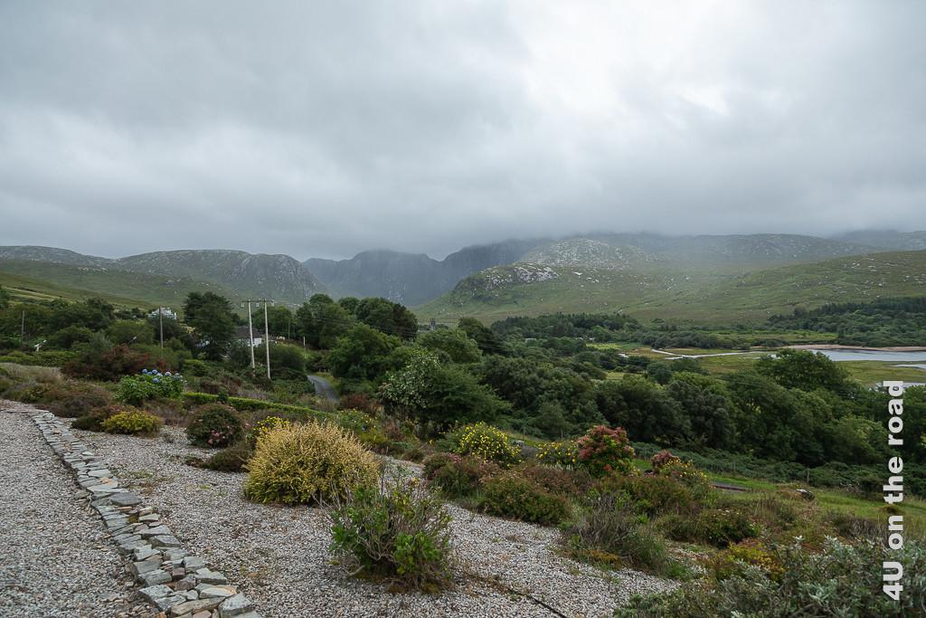 Bild Blick von unserer Terrasse in Dunlewey Richtung Poison Glen zeigt das Ende des Ortes Dunlewey mit der Kirchenruine, dem Ende des Sees und den blühenden Büschen im Garten.