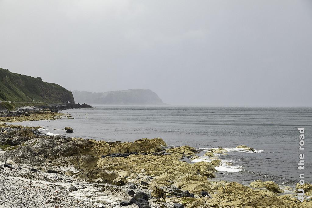 Bild Auf dem Weg nach Ballycastle entlang der Küste zeigt die Küstenstrasse unterhalb der hohen Klippen am Meer