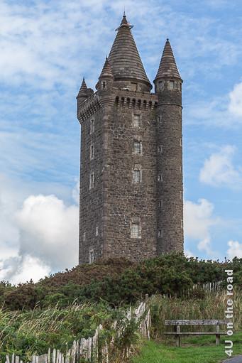 Bild Scrabo Tower, Newtownards zeigt den viereckigenTurm auf dessen rechter Seite ein Rundturm angebaut ist, mit seinen Türmen in der Mitte und auf jeder Ecke. Im Vordergrund sieht man eine Bank, die zum Ausruhen einlädt.