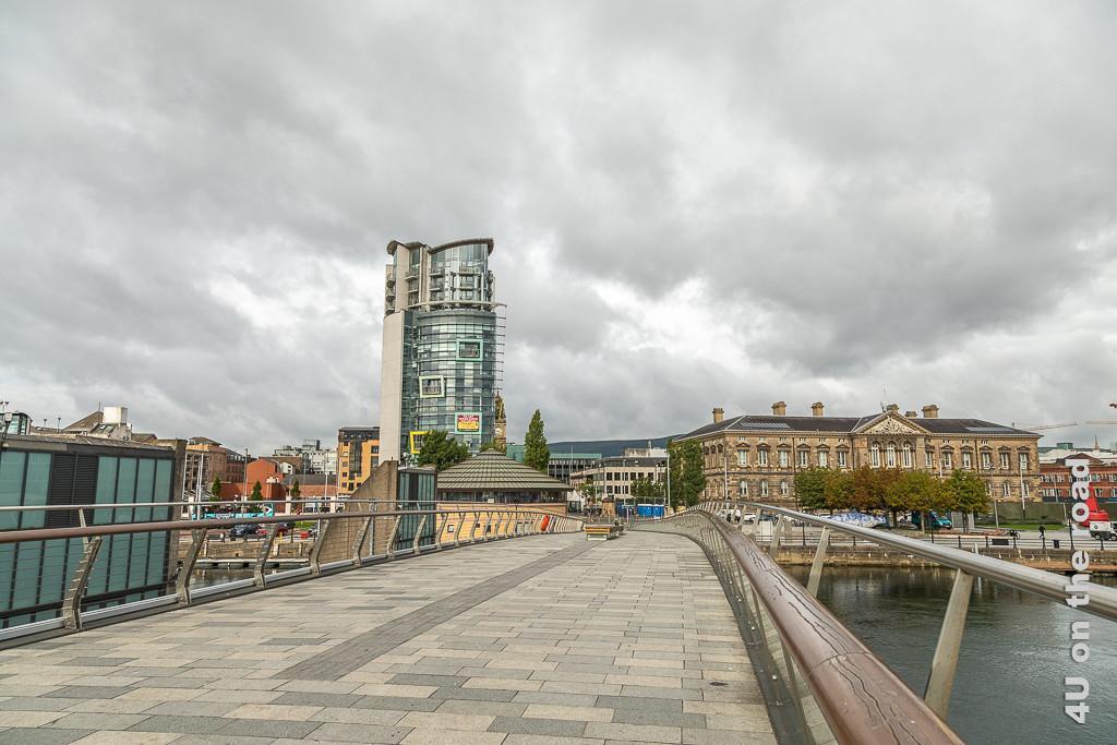 Bild Blick zurück vom Ufer des Titanic Viertels in die Stadt, Belfast zeigt die Brücke, einen lustigen Büroturm, der wie Bilderrahmen aussen hängen hat. Auf der anderen Seite der Brücke steht ein grosses Haus aus dem letzten Jahrhundert.
