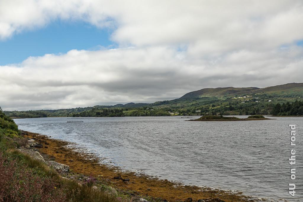 Bild Am Broad Water zeigt neben Inseln im Fjord auch eine Fischzuchtstation. Das Wasser ist von Hügeln umgeben.