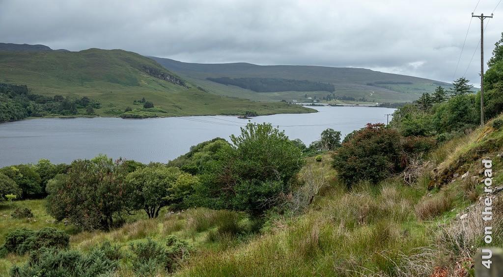 Bild Blick von unserer Terrasse in Dunlewey in Richtung Lough Nacung Upper bei Dunlewey zeigt den länglichen See mit seinem Damm eingebettet in grüne Hügel auf der einen Seite und verwildertem Garten auf der anderen Seite.