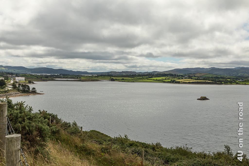 Bild Blick zurück auf den Brod Water See zeigt ein Ufer mit sonnenbeschienen Feldern in gelb un grün, Dämme im See und scheinbar Seen hinter dem See.