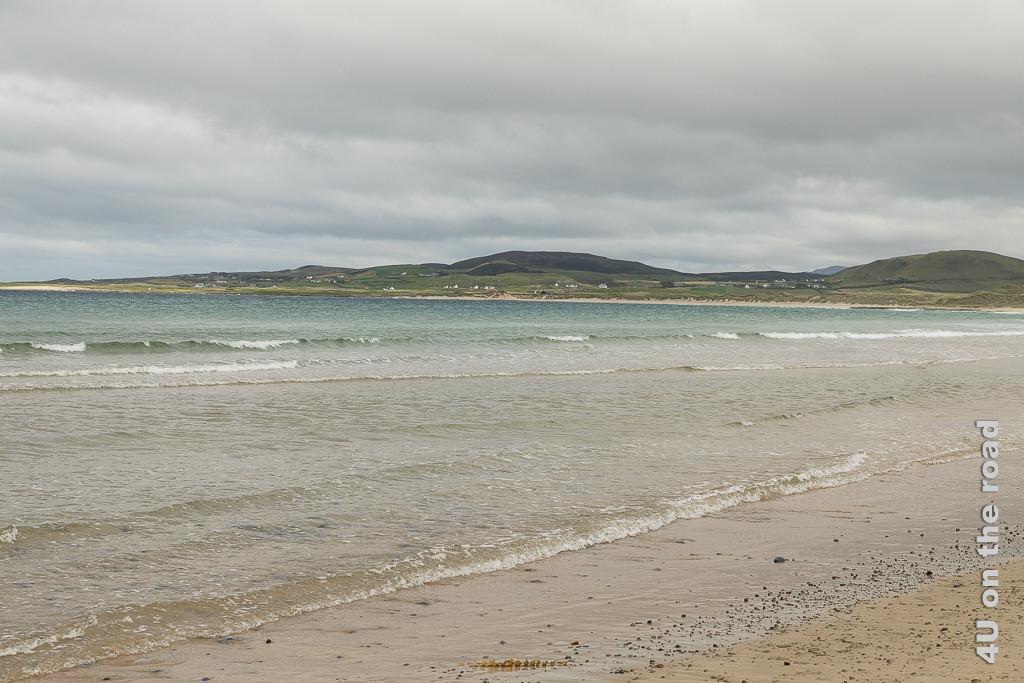 Am Strand der Ballyhiernan Bay, Fanad Peninsula zeigt die grosse Bucht mit ihrem Sandstrand und den Dünen. Wellen rollen an den Strand, im Hintergrund erheben sich Hügel.