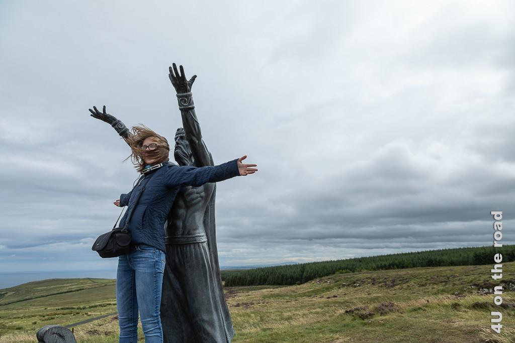 Bild Im Windschatten der Skulptur am Gortmore Viewpoint, Bishops Road Titanic spielen, zeigt Gwendolyn vor der Skulptur des Meeresgottes mit ausgebreiteten Armen , die Haare vom Wind verweht.