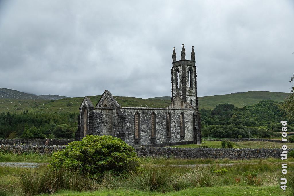 Bild Dunlewey Kirchenruine zeigt die von einer Mauer umgebene Ruine einer gotischen Kirche, deren Äussers noch ohne Dach komplett steht. Im Hintergrund erheben sich grüne Hügel.