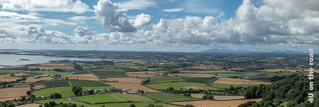 Bild Panoramablick auf den Strangford Lough zeigt eine Welt aus kleinen Feldern in verschiedenen Grün- und Gelbtönen und den Stranford Lough. Im Hintergrund erheben sich Berge.