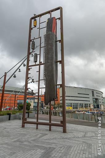 Bild Titanic Skulptur Belfast Marina zeigt ein an einem hohen Geländer aufgehängtes Titanic Schiff.