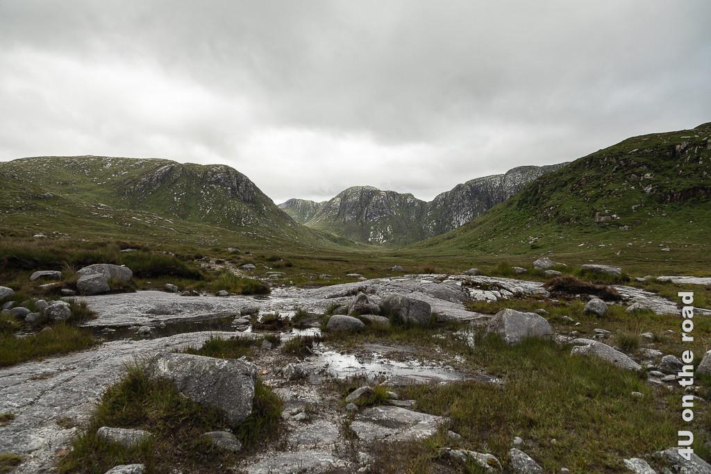 Bild Blick zum Poison Glen, Dunlewey zeigt im Vordergrund den steinigen, nassen Weg und im Hintergrund erheben sich die Berge.