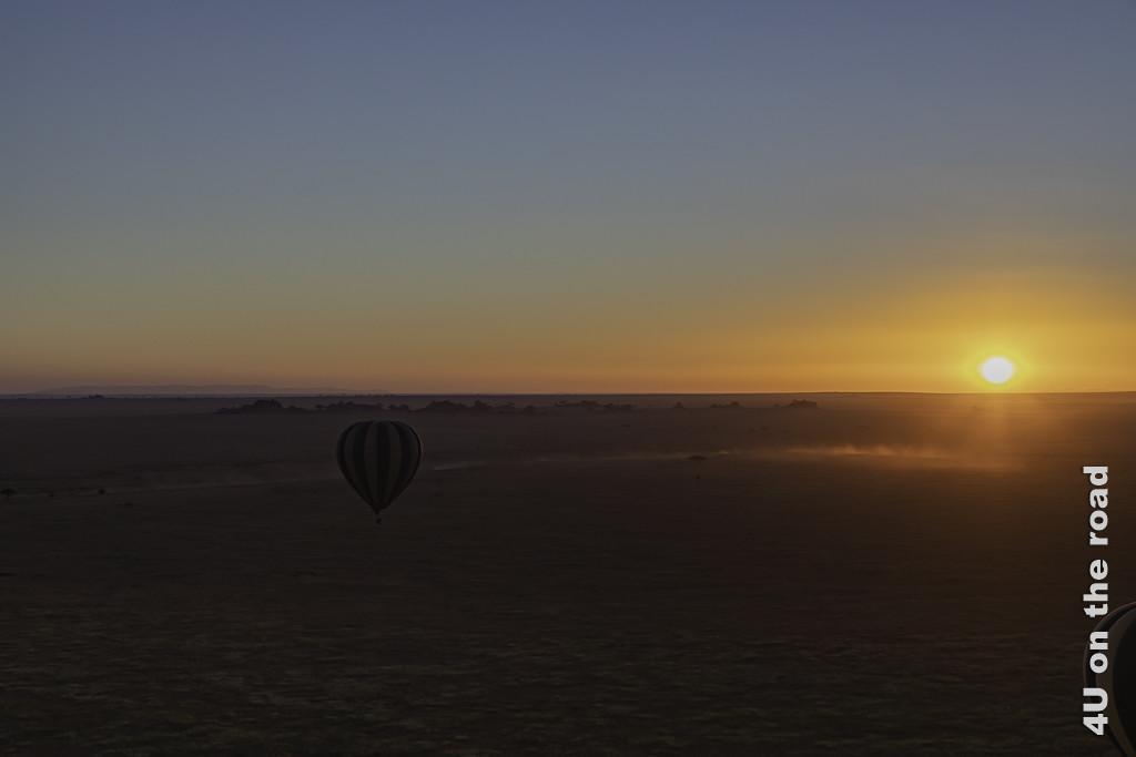 Bild Ballonfahrt - Die Sonne geht über der Serengeti auf zeigt einen im Dämmerlicht vor uns schwebenden Ballon über der grossen Ebene, die runde Sonne, die gerade hinter dem Horizont auftaucht und aufgewirbelten Staub von einem fahrenden Fahrzeug