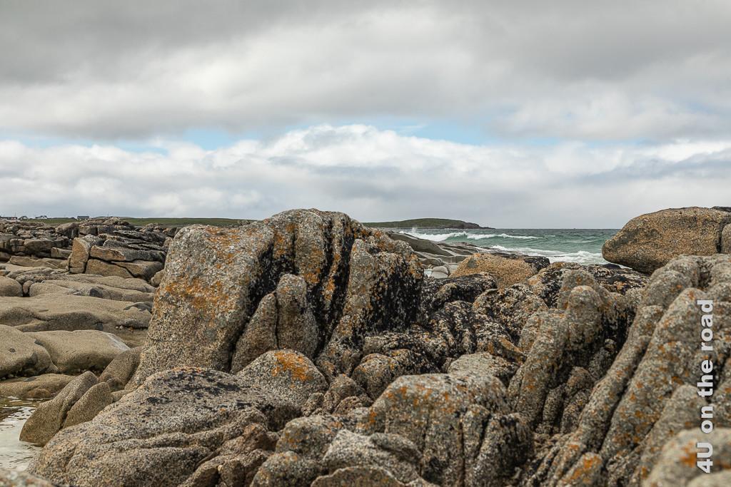 Bild Felsen unterbrechen den Strand an der Ballyhiernan Bay, Fanad Peninsula zeigt zerfurchte, Flechtebewachsene Steine und im Hintergrund sich brechende Wellen.