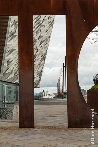 Bild Titanic Museum mit Kreuzfahrtschiff, Belfast zeigt durch das I des rostigen Schriftzuges fotografiert ein vor Anker liegendes Kreuzfahrtschiff.