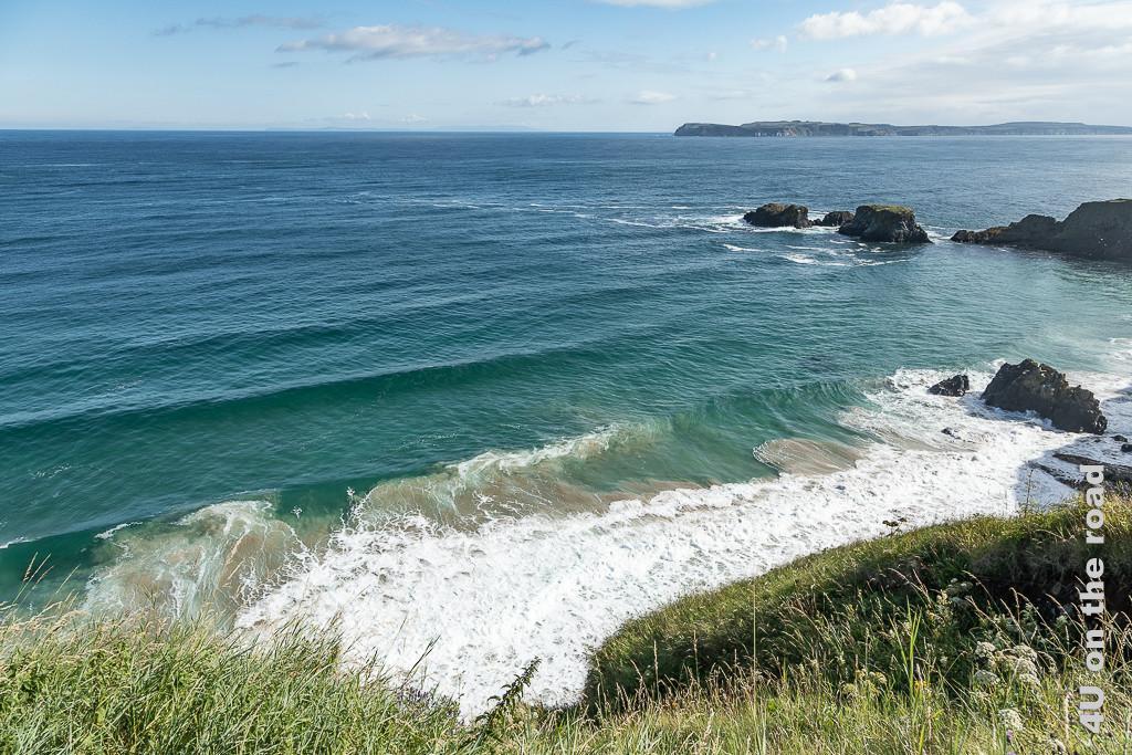 Bild Sandfahnen im Wasser auf dem Weg zur Carrick-a-Rede Rope Bridge zeigt wie die Wellen Sand vom Boden mitnehmen