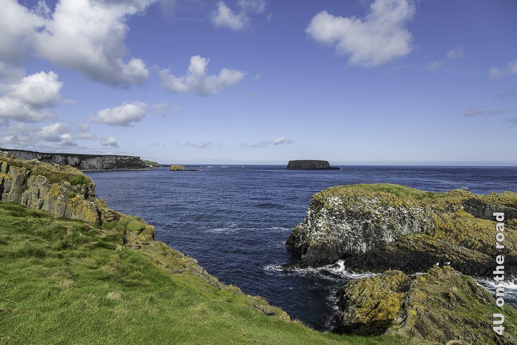 Blick von Carrick-a-Rede Island zeigt hohe Klippen und einzelne Felsen im Wasser