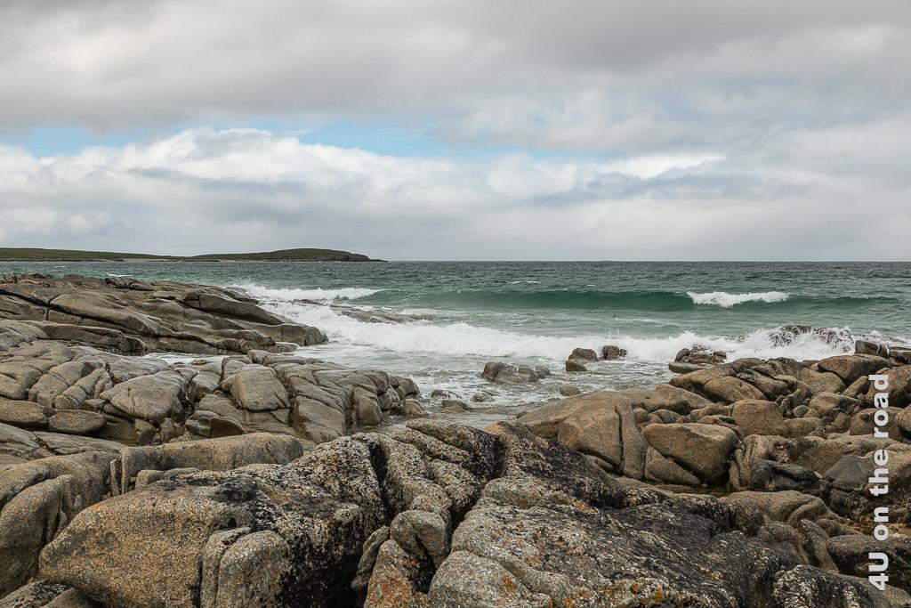 Bild Felsen und Meer, Ballyhiernan Bay, Fanand Peninsula zeigt wie rund geluschte, zerfurchte, niedrige Felsen ins Wasser wachsen. Die Wellen rollen brechend darauf zu.