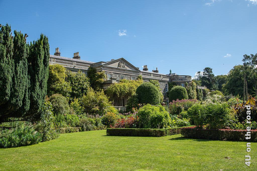 Bild Italienischer Garten, Mount Stewart zeigt den Garten von der unteren Ecke mit Blick auf das Herrenhaus. Auf dem Rasen stehen quadratische Beete mit verschiedenen Blütenpflanzen. Die Beete sind von einer niedrigen Hecke eingefasst. Rund geschnitte Bäume stehen rechts und links der Treppe.
