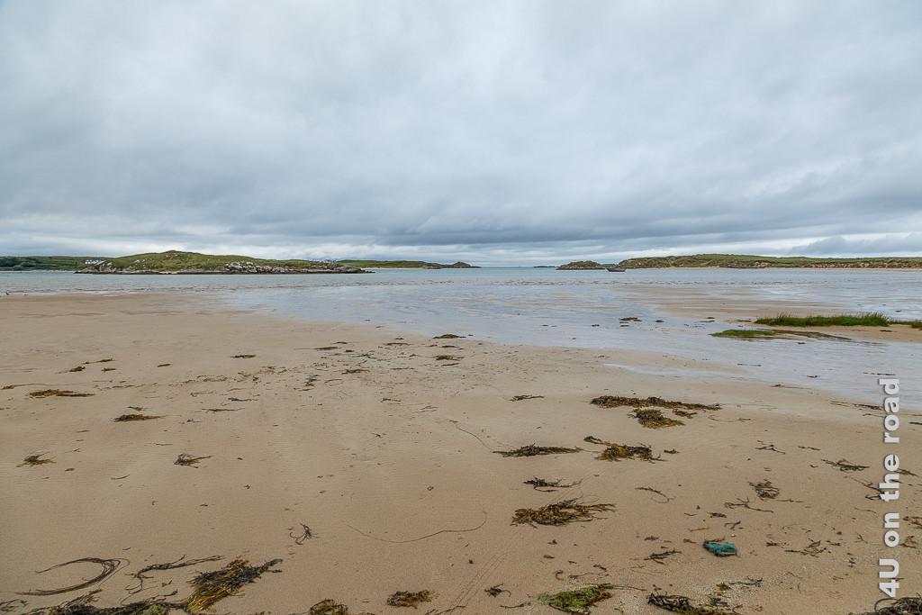 Bild Strand bei Ebbe in Bunbeg zeigt den feuchten, teilweise noch von einer dünnen Wasserschicht bedeckten Strand. Aus dem Wasser ragen mehrere Inseln heraus.
