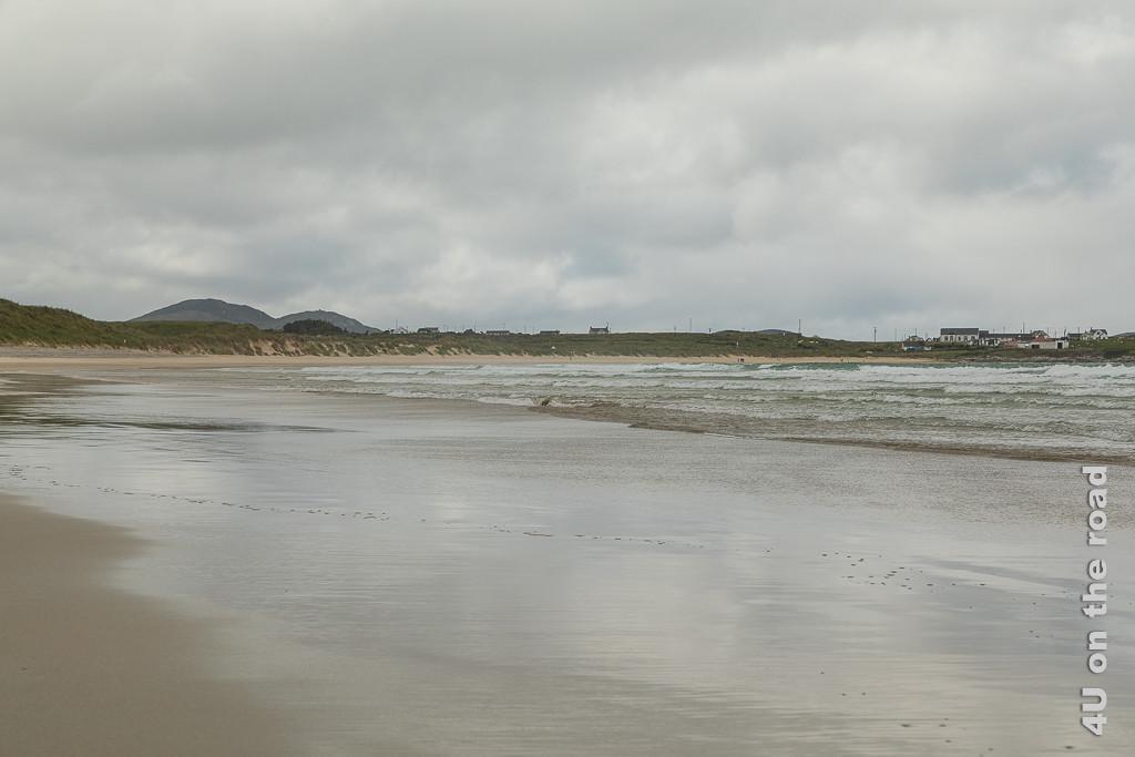 Bild Ballyhiernan Bay Sandstrand, Fanad Peninsula zeigt den breiten Sandstrand auf dem sich auf einem dünnen Wasserfilm die Wolken spiegeln und auf den viele Wellen zurollen.