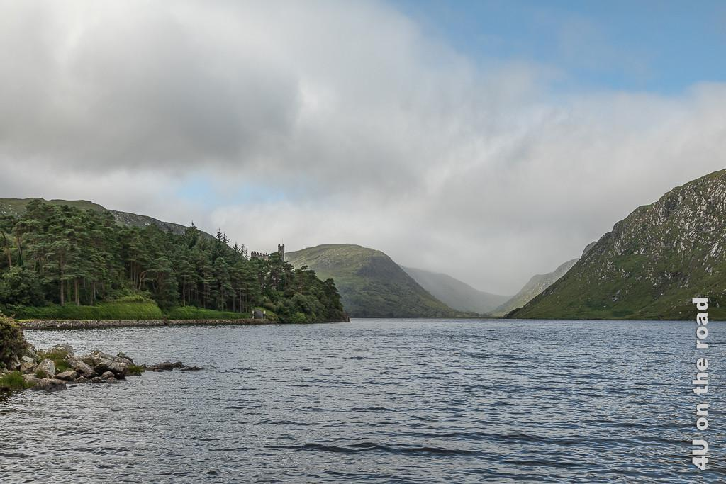 Bild Glenveagh NP - Blick auf das Schloss zeigt scheinbar aus dem See aufgenommen, das über den Bäumen thronende Schloss. Im Hintergrund Bege und Wolkenschleier, die hereinziehen.