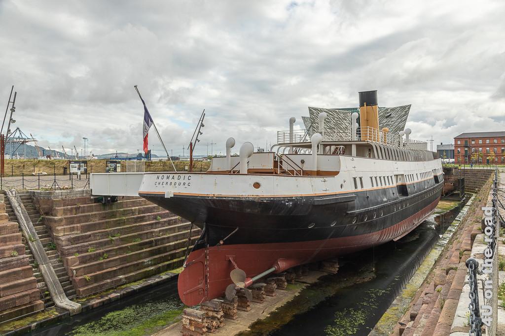 Bild Nomadic im Trockendock - Belfast zeigt das Schiff von vorn. Im Hintergrund ragt das Titanic Museum in den Himmel