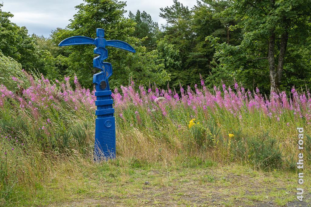 Bild Wegweiser zeigt einen eigenwillig geformten tiefblauen Wegweiser mit zwei Armen, wie ein Kleiderbügel. Der Wegweiser besteht aus Metall und bildet einen starken Kontrast zu den pink blühenden Blumen vor dem Hintergrund des dunkelgrünen Waldes.