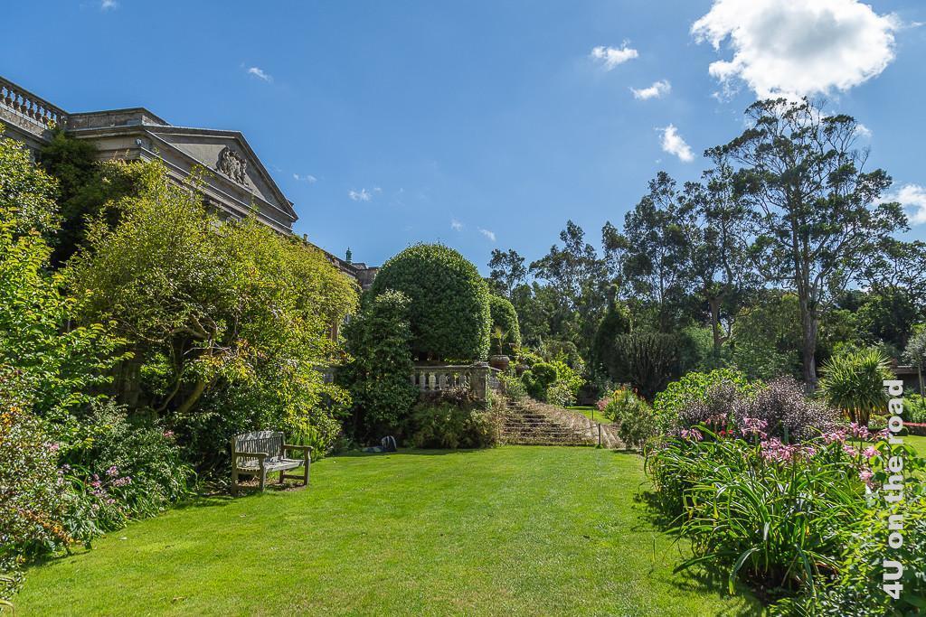 Im italienischen Garten, Mount Stewart zeigt eine seitliche Aufnahme in Richtung Freitreppe des Gartens. Links wachsen höhere Büsche und Blumen an der Hausmauer. Eine Bank steht im Schatten. Rechts blickt man auf eines der formalen Beete mit rosa blühenden Zwiebelpflanzen.