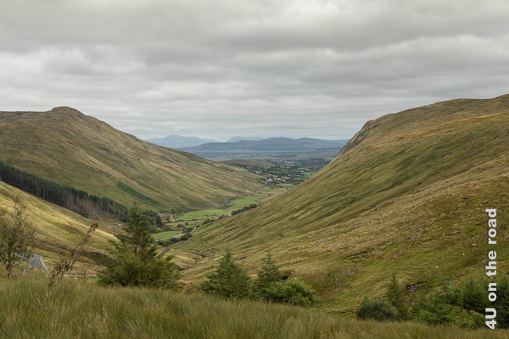 Bild Blick vom Aussichtsparkplatz zurück zeigt das langgezogene Tal und im Hintergrund weisse Häuser und weitere Bergketten.