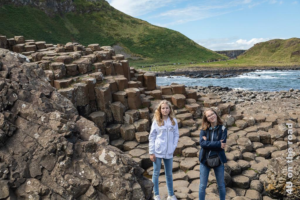 Giants Causeway - ein paar Basaltsäulen für uns zeigt die beiden Töchter auf sechseeckigen Basaltsäulen. Im Hintergrund sieht man den Weg mit Massen von Leuten