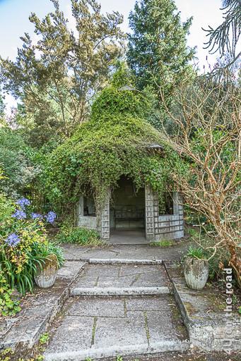 Bild Gartenhaus im Mairi Garten, Mount Stewart zeigt die Stufen zum überwucherten Gartenhaus und. Auf dem Dach lässt sich der Taubenschlag noch ahnen.