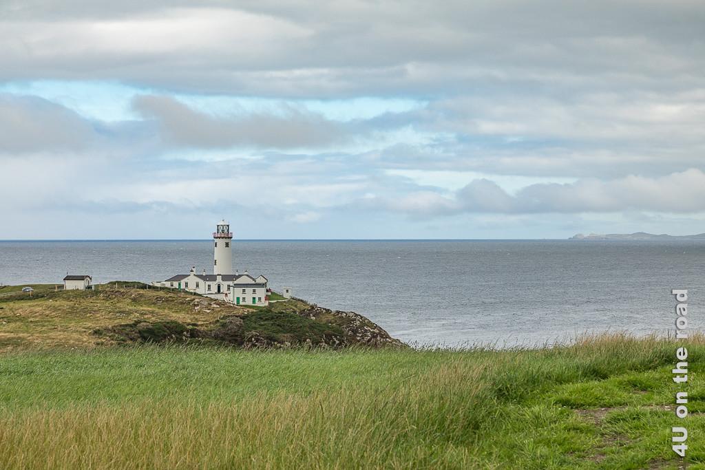 Bild Fanad Peninsula - Leuchtturm zeigt den weissen Leuchtturm mit dazugehörigen Häusern auf der Landspitze. Im Vordergrund sind hohe Gräser zu sehen.